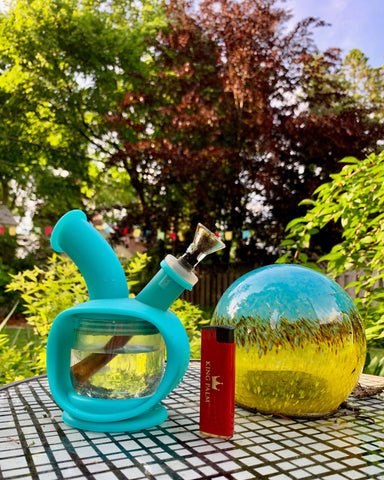 The Teal Ooze Kettle is sitting on an outdoor table next to a red King Palm lighter and teal and yellow decorative glass ball. There are tall trees in the background.