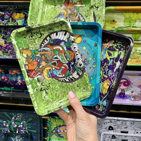 A female hand holds the Ooze Band Jam, Tree of Life, and Universe small rolling trays in front of a wall of other rolling trays.