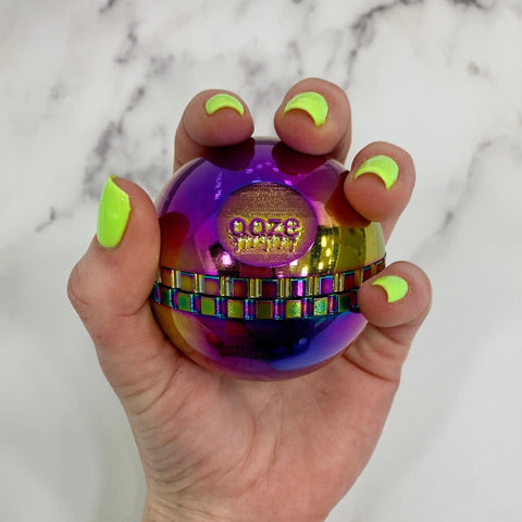 A white female hand with bright green nails holds the new Rainbow oil slick Ooze Saturn globe grinder in her left hand against a white marble background.