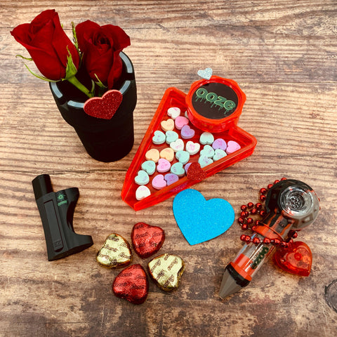 "The Ooze Valentine's ""His"" bundle lays on a wood surface. The red grinder tray is filled with conversation hearts, the bowser bowl has a heart necklace draped over it, the black roadie has 2 roses in it, the EZ pipe lays on it's side and there is a blue glitter heart and 4 chocolate hearts."