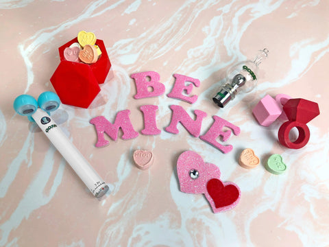 The Ooze Valentine's Bundle is laying flat on a light pink and white tie dye background. The white Slim Twist vape battery is ot the left with a blue pair of googly eyes on it. The red Geode stash jar is filled with conversation hearts, and the Cloud glass globe is in the top right. There are a few other heart stickers and conversation hearts