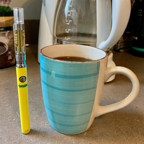 The yellow Ooze Slim Twist Vape Pen Battery is standing upright on a counter with a full cartridge attached. It is next to a full mug of coffee, with the white coffee pot in the background.