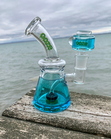 The aqua teal Ooze Glyco freezable water pipe sits on the end of a dock in Lake Michigan. The water is a steely blue gray, and the sky is cloudy.