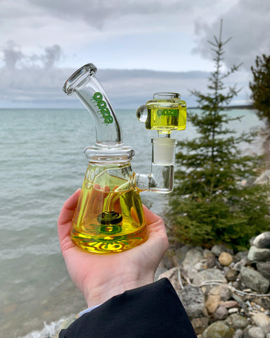 A white female hand holds the Mellow Yellow Ooze Glyco Glycerin Water Pipe outside. In the background, there is a lake, pine tree, and you can see part of a beach.