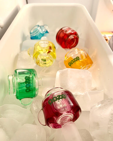 All 6 colors of the Ooze Glyco freezable bowls are placed in an ice tray in a freezer, with ice cubes mixed in.