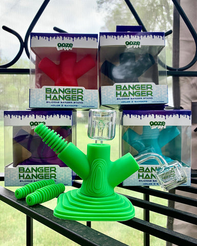 All 5 Ooze Banger Hangers are displayed. The green one is out of its box, with two bangers inserted and two adapters laying next to it. The rest of the pieces are in their original packaging, stacked behind the green one.
