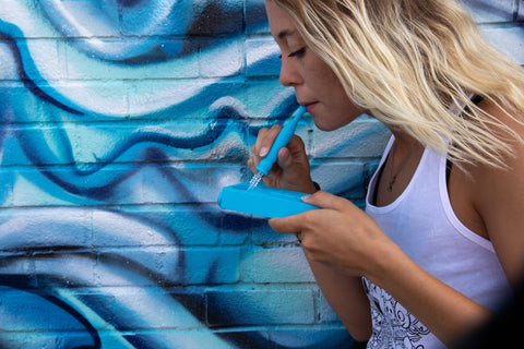 A young blonde female takes a dab with the Ooze Slugger Dabbin Dugout in teal. She wears a white tank top and is standing in front of a wall with a blue painted mural.
