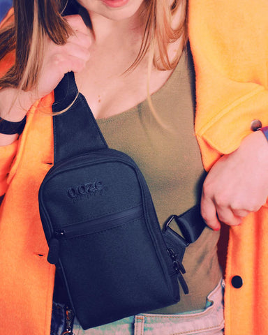 A young white woman is wearing the Ooze Smell Proof Crossbody Bag in black. She is wearing a hunter green tank top, lightwash jeans and a bright orange shacket. She is grabbing both the top and side straps to adjust the bag.