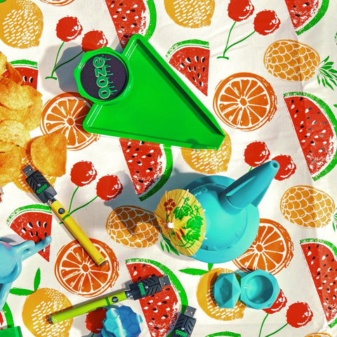 Ooze products are laid out on a picnic tablecloth with a fruit pattern. There is a green Grinder Tray, teal UFO and Geode, a green and yellow Slim Twist battery, and an Ocean honey pot.
