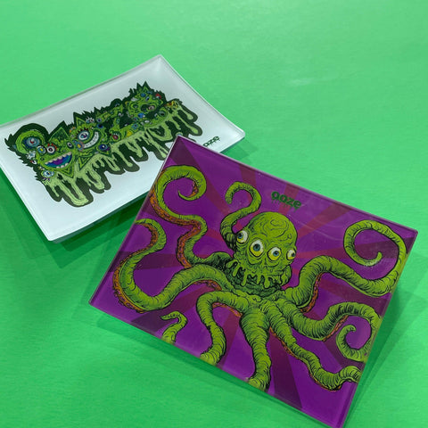 A small shatter-resistant glass rolling tray with the Ooze Imaginarium design is shown against a green background. The Oozemosis design is shown at the top of the stack in the background.