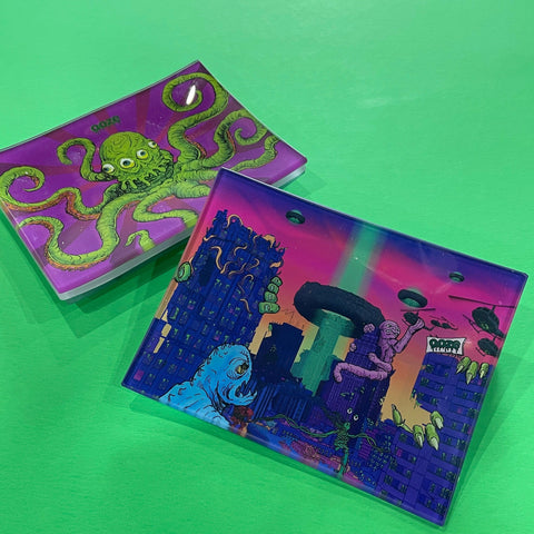 A small shatter-resistant glass rolling tray with the Ooze After Hours design is shown against a green background. The Sir Inks-a-Lot design is shown at the top of the stack in the background.