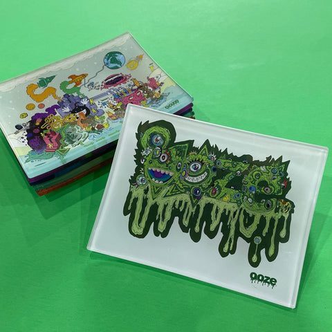 A small shatter-resistant glass rolling tray with the Ooze Oozemosis design is shown against a green background. The Imaginarium design is shown at the top of the stack in the background.