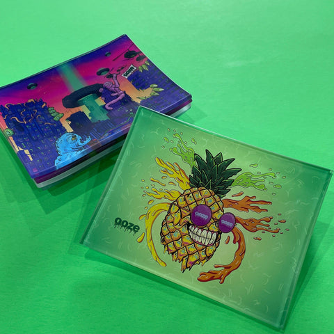A small shatter-resistant glass rolling tray with the Ooze Mr. Pineapple design is shown against a green background. The After Hours design is shown at the top of the stack in the background.