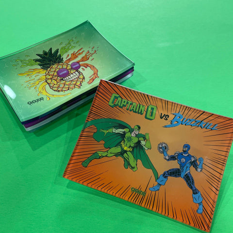 A small shatter-resistant glass rolling tray with the Ooze Fight design is shown against a green background. The Mr. Pineapple design is shown at the top of the stack in the background.
