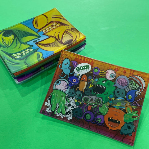 A small shatter-resistant glass rolling tray with the Ooze Monstrosity design is shown against a green background. The Face Off design is shown at the top of the stack in the background.