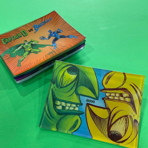 A small shatter-resistant glass rolling tray with the Ooze Face Off design is shown against a green background. The Fight design is shown at the top of the stack in the background.