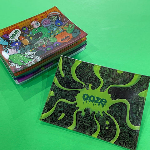 A small shatter-resistant glass rolling tray with the Ooze Abyss design is shown against a green background. The Monstrosity design is shown at the top of the stack in the background.