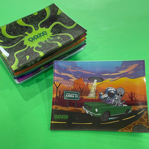A small shatter-resistant glass rolling tray with the Ooze Space Race design is shown against a green background. The Abyss design is shown at the top of the stack in the background.
