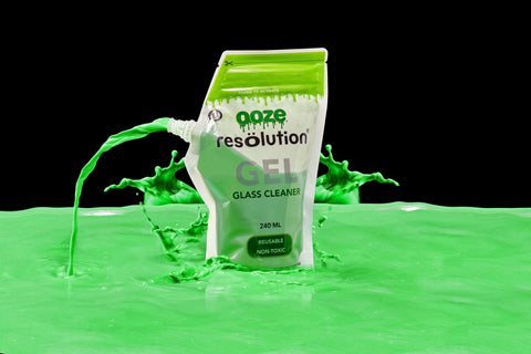A pouch of green Ooze Resolution cleaning gel is sitting in a big puddle of green gel. The cap is removed and cleaning gel is spewing out of the spout like a fountain, and there are splashes all around the bag. The background is black.