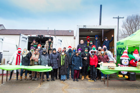 A group shot of the Ooze team in front of the trucks and tents for the Oozemas holiday toy drive in Detroit. Everyone is bundled up in winter clothes and everyone has a face mask on.