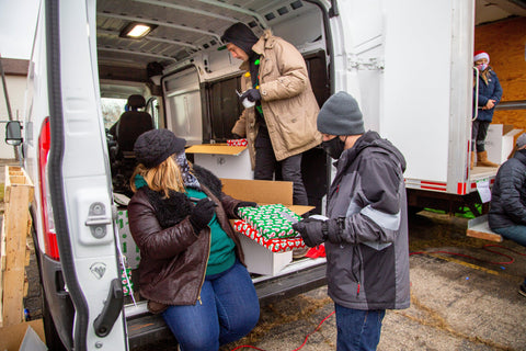 A woman and two men are working at the Oozemas holiday toy drive. They are grabbing gifts that are organized in bins in the back of a white van, and writing the gender and ages of each wrapped gift to give away.