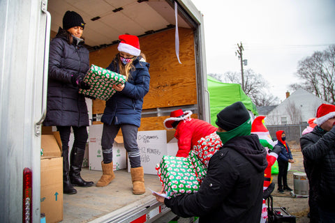A group of Ooze workers are unloading gifts from a truck at the Oozemas holiday toy drive. A young girl in a Santa hat is writing on a gift with green wrapping, and others are waiting to be handed gifts to distribute.