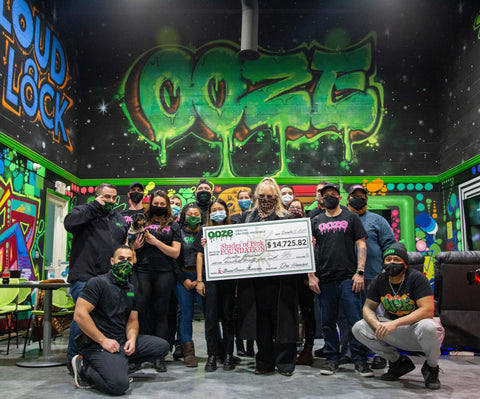 Shades of Pink Foundation Executive Director Karla Sherry stands with the Ooze team in the Ooze breakroom. She is holding the huge check made out for $14,725.82, and everyone is wearing face masks.