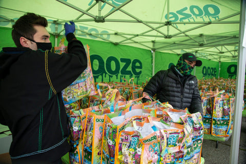 Two guys in face masks and winter clothes are under the green Ooze tent at the Oozegiving Food Drive. They are handing out Ooze bags filled with side dishes.