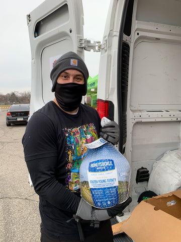 A white man with black face mask, gray beanie, and black clothes holds up a frozen Turkey at the Oozegiving Food Drive event.