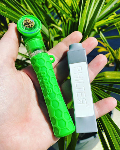 A white female hand holds the green Ooze Piper hand pipe and chillum with a small white and silver air filter. Her hand is outside above a green, leafy fern.