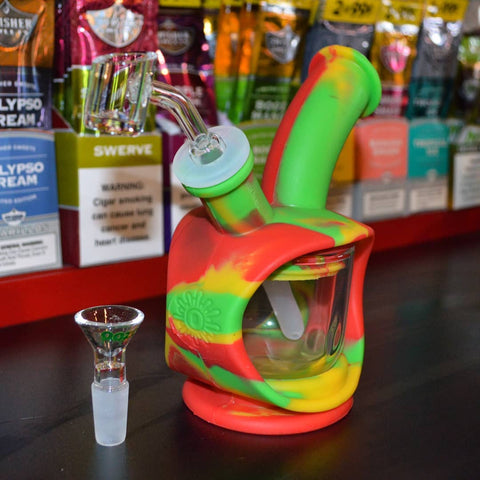 The Rasta Ooze Kettle is on a black counter in a smoke shop, in front of a display of different blunt wraps and rolling papers. The quartz banger is inserted in the piece, and the flower bowl is standing up to the front left of the Kettle.