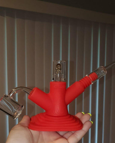 A female hand holds the red Ooze Banger hanger in her hand. All three branches have a banger inserted. Two are male, and on the right is a female connected to a ribbed silicone adapter.