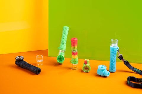 Four Ooze Pipers are displayed together in a colorful scene. The floor is orange and walls are green and yellow. There is a black, green, rasta, and teal Piper displayed in different positions and are shown as either a hand pipe or a chillum with the spare accessories scattered around.