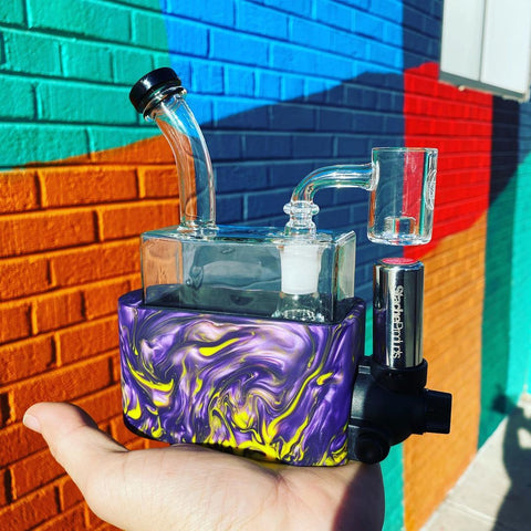 The purple mix Stache Products RiO Rig-in-One portable dab rig is sitting in the palm of a hand. The person is outside, standing next to a colorful, geometric mural.