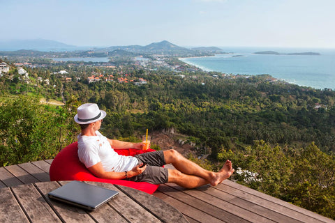 A man in summer clothes and a gray fedora sits on a beanbag with a drink, relaxing on a hilltop with his laptop on a table, closed behind him. He is unwinding after a long day of working from home.