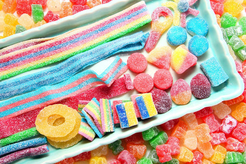 A large assortment of different sour candies fills the frame. There is a tray with sour belt candies, rings, and smaller sour candies. Around the tray are tons of red, orange, yellow and green sour gummy bears.
