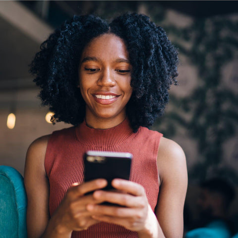 A young black woman with shoulder length curly hair is sending an email on her cell phone.