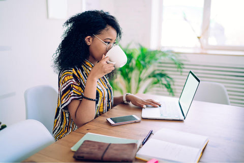 A young black woman drinks her morning coffee from a white mug while sitting at a light wood table in front of her laptop. She has other work supplies as she works from home.