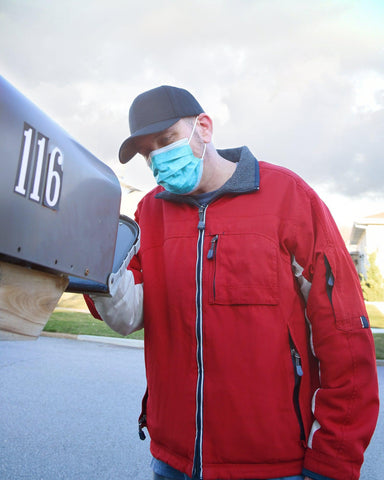 A man wearing a red jacket, black baseball cap, and blue face mask opens his mailbox to check to see if he has received a package.