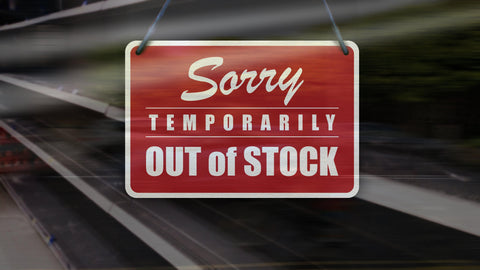 """A red sign with white letters that read """"Sorry temporarily out of stock"""" is hanging in a window in front of empty shelves"""
