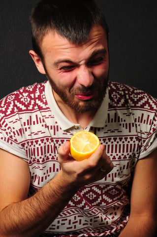 A white guy with brown and hair and a beard puckers his face eating a lemon. He's wearing an Aztec print red and white t shirt and is against a black background.