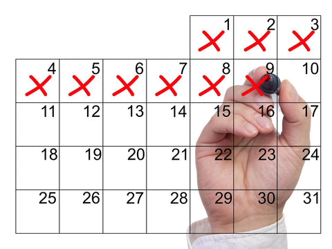 A white male hand crosses days off a transparent calendar with a red marker.