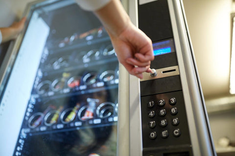 A white hand is pressing the enter button on a vending machine to purchase a snack.