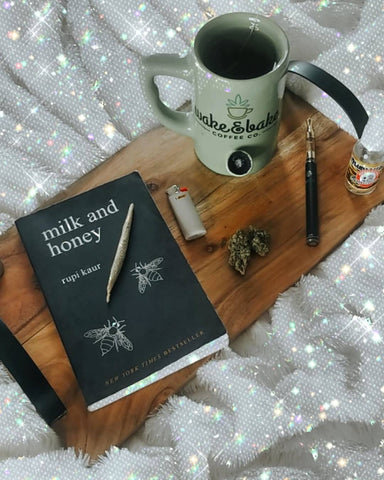 A wood tray is resting on a bed. The tray has a black poem book, wake and bake mug with a pipe built in, a lighter, nug of cannabis, and black Ooze slim twist vape pen.