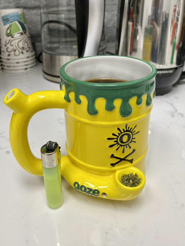 The yellow Ooze Toxic Waste Barrel Mug Pipe is sitting on a white granite counter with a small, light green Clipper lighter to the left. The bowl is packed with flower and the mug is filled with coffee. There is a silver metallic coffee carafe in the background.