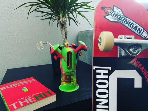The Ooze Rasta Trip 2-in-1 Water Pipe is sitting on a black side table with the banger inserted. It is next to a red book and you can see the underside of a skateboard deck.
