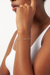 dainty thin chain bracelet with five cz stones spread out in gold on model