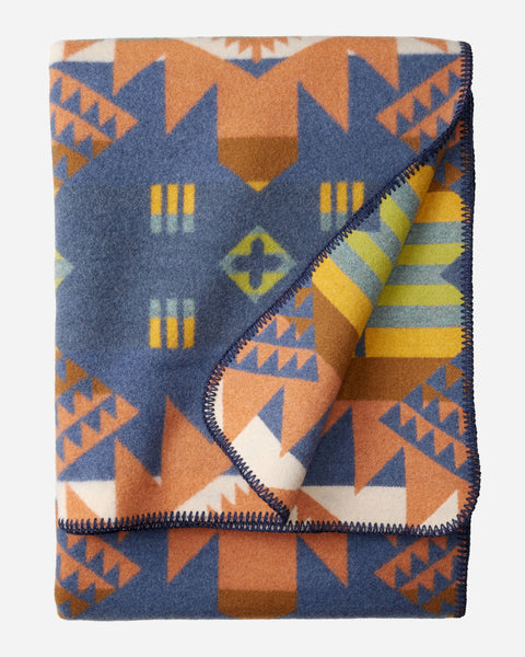 Pendleton wool blanket, ivory, oranges and blues in geometric patterns, called Journey West.