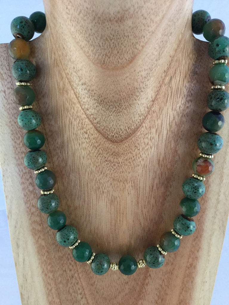 Babs II:  has green ceramic and faceted green/rust Agate with gold metal inserts and toggle