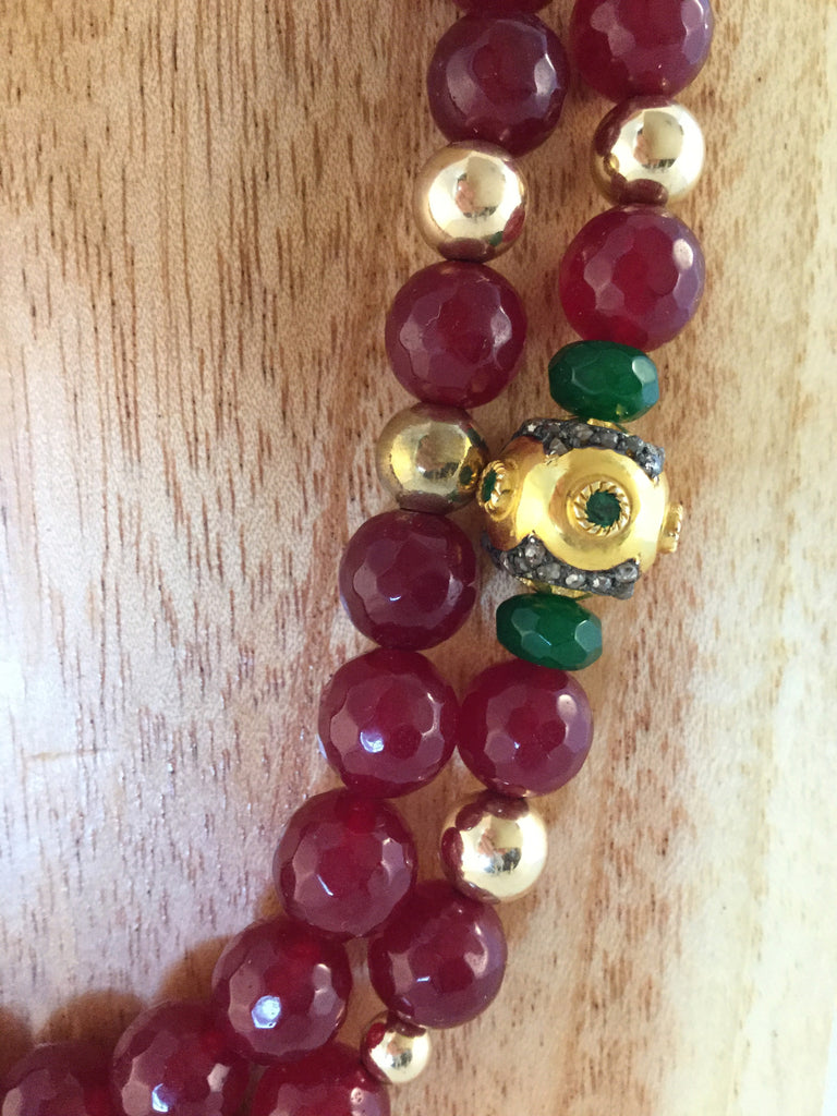 RUBY: solid Gold & emerald bead, surrounded by Emeralds.